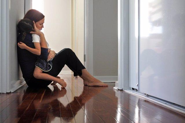 Archivo - Mujer sentada en el suelo del pasillo abrazando a su hija. Depresión, dolor, trauma.