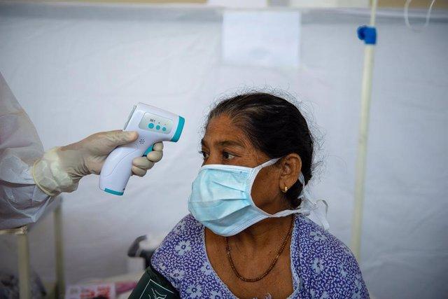 Toma de temperatura a una mujer en India durante la pandemia de coronavirus