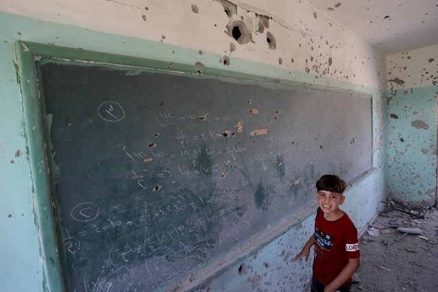 27 May 2021, Palestinian Territories, Gaza City: APalestinian boy inspects a classroom at a school previously hit by Israeli airstrikes on Gaza City. Israel and the Palestinian Islamist movement Hamas have so far been keeping to an agreed ceasefire that