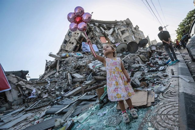 25 May 2021, Palestinian Territories, Gaza City: A girl holds balloons near the Hanadi Tower in the middle of Al-Rimal Market, one of the buildings damaged in Israeli air strikes. Photo: Mohammed Talatene/dpa