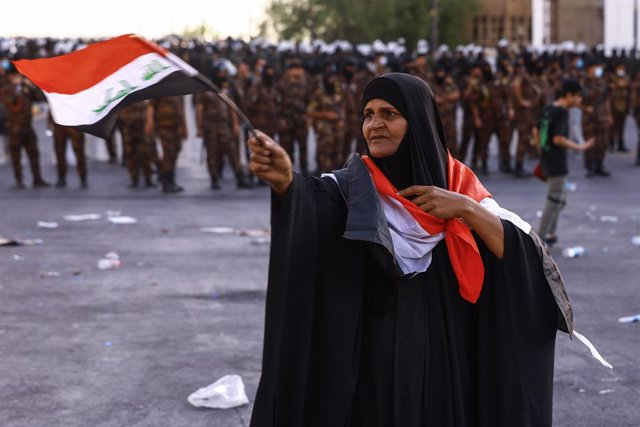 25 May 2021, Iraq, Baghdad: A woman with Iraqi flag takes part in an anti-government protest calling for the killers of pro-reform activists to be revealed. Photo: Ameer Al Mohammedaw/dpa