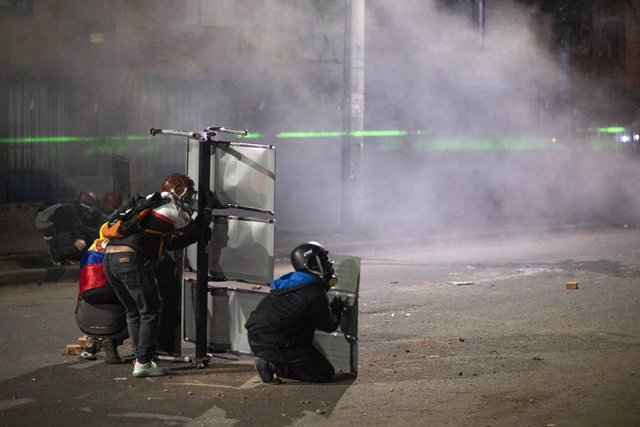 26 May 2021, Colombia, Bogota: People take cover behind shields during clashes with riot police at a protest against the government of Colombian President Ivan Duque Marquez. Photo: Daniel Garzon Herazo/ZUMA Wire/dpa