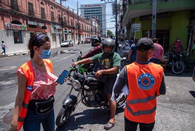 Trabajadores de la Comisión Permanente de Contingencias realizan labores de prevención del coronavirus en San Pedro Sula.