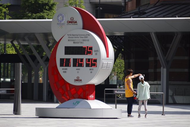 09 May 2021, Japan, Tokyo: People take a photo near Tokyo 2020 Olympic Games countdown clock outside Tokyo station. Tokyo reported 1,121 new cases of coronavirus (COVID-19) on Saturday, the highest number since 22 January 2021. On Friday, Japan's Prime Mi