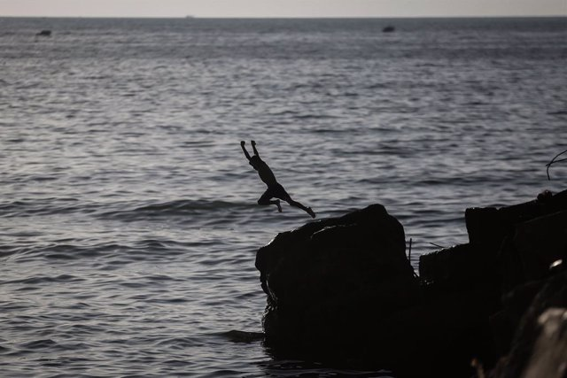 27 May 2021, Palestinian Territories, Gaza City: A Palestinian jumps on the water of the Mediterranean, as life begins to return to normalcy, after a ceasefire was reached last week after 11 days of deadly confrontations between Israel and the Palestinian