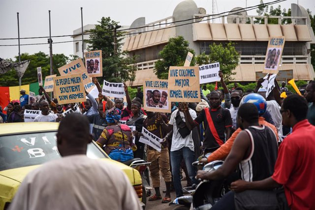 28 May 2021, Mali, Bamako: Supporters of Malian Armed Forces (FAMA) hold placards during a protest at Independence square in Bamako, against the expense of current French policy and to celebrate the recent coup led by the vice president of the transitiona
