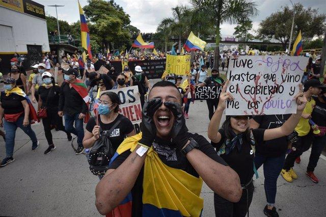 Manifestantes gritan consignas contra el Gobierno al pasar frente a la Universidad Santiago de Cali durante una protesta contra la Administración de Iván Duque.