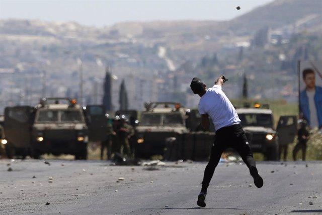 Un manifestante palestino frente a fuerzas militares israelíes en Cisjordania