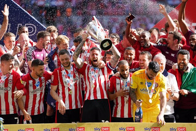 29 May 2021, United Kingdom, London: Brentford's Pontus Jansson (C) lifts the trophy as they celebrate promotion to the Premier League after winning the English EFL Championship play-offs final soccer match between Brentford and Swansea City at Wembley St