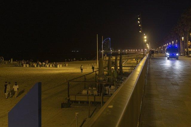Un coche de policía vigila la playa de la Barceloneta durante el primer viernes sin toque de queda, a 14 de mayo de 2021, en Barcelona, Catalunya, (España).