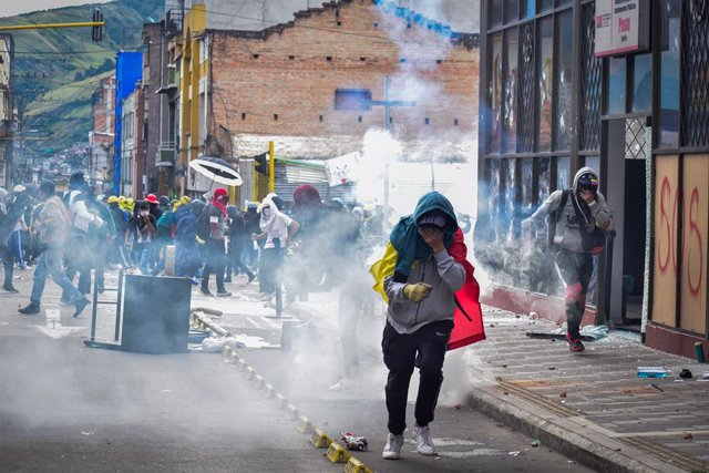 28 May 2021, Colombia, Pasto: Demonstrators run from tear gas during clashes with riot police following a protest against the government of President Ivan Duque Marquez. Colombian President Ivan Duque on Friday night said military assistance would be sent