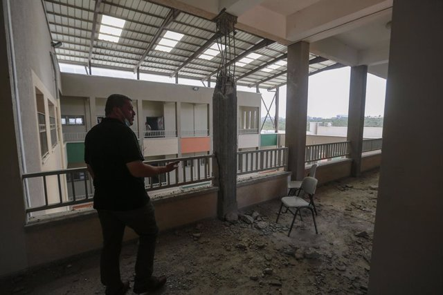 30 May 2021, Palestinian Territories, Gaza City: An employee of the Palestinian Ministry of Education inspects one of the damaged corridors of a school that was hit during the recent Israeli airstrikes on the Zeitoun neighbourhood in Gaza City. Israel and