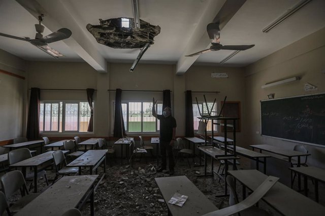 30 May 2021, Palestinian Territories, Gaza City: An employee of the Palestinian Ministry of Education inspects a hole in the ceiling of a damaged classroom at a school that was hit during the recent Israeli airstrikes on the Zeitoun neighbourhood in Gaza