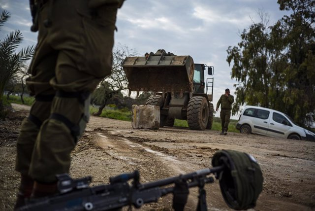 Archivo - 26 March 2019, Israel, Nahal Oz: An Israeli soldier stands next to his machine gun as a bulldozer deploys near the Israel-Gaza border after a long night of rocket attacks and bombing on both sides. Photo: Ilia Yefimovich/dpa