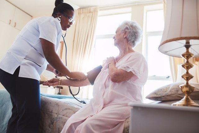 Archivo - Female nurse checking blood pressure of a senior woman