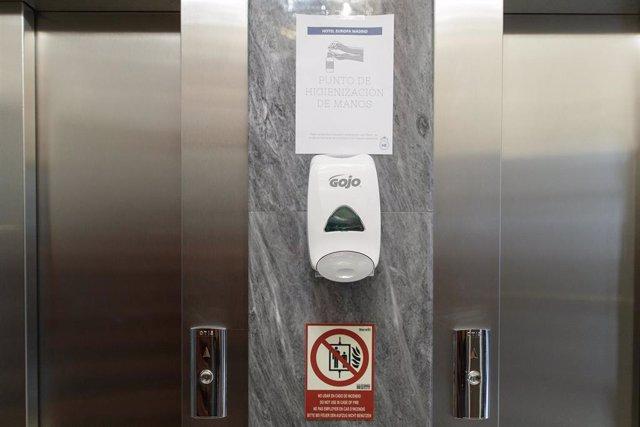 Archivo - Puerta de un ascensor con un cártel que invita a lavarse las manos y un dispensador de jabón