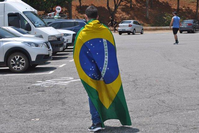 Archivo - Un joven ataviado con la bandera de Brasil.