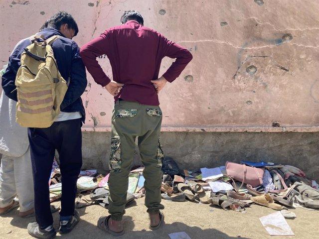 Dos personas inspeccionan el lugar del atentado contra una escuela femenina en la capital de Afganistán, Kabul