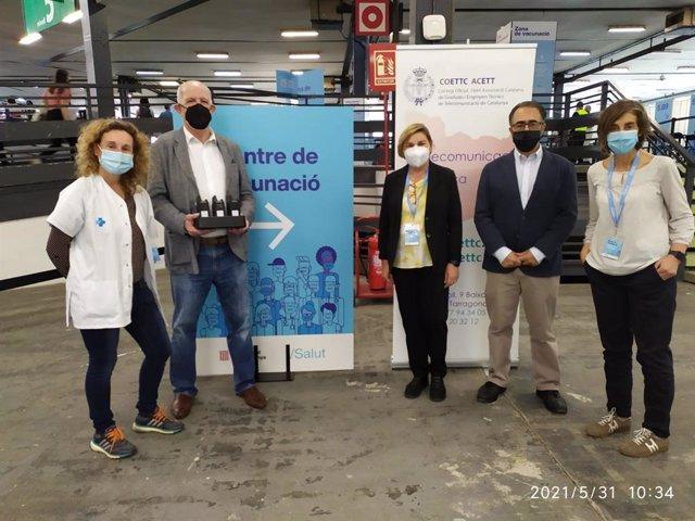 El president de Telecos.cat, Pedro Linares, i el degà del COETTC, Jordi Farré, amb l'equip professional del centre de vacunació de Fira Barcelona aquest dilluns.
