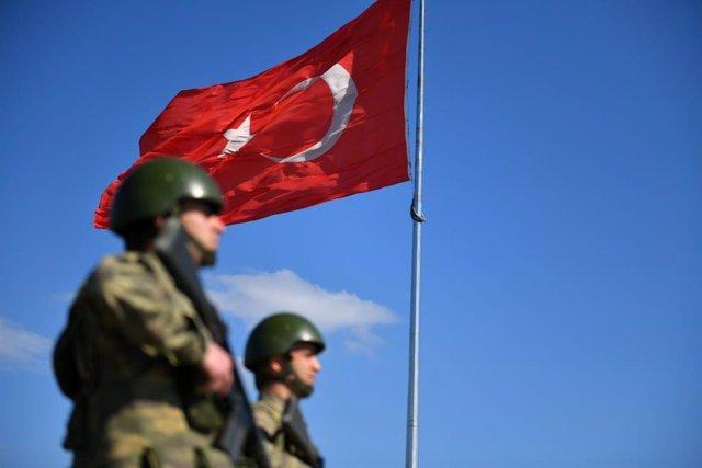 Militares bajo una bandera de Turquía
