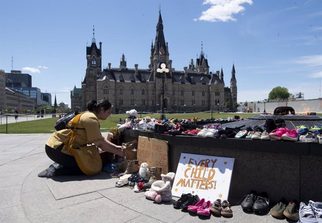31 May 2021, Canada, Ottawa: An indigenous kneels in front of shoes placed on the Centennial Flame to honour more than 200 children whose remains have been found buried at a former residential school in Kamloops. Photo: Adrian Wyld/The Canadian Press via