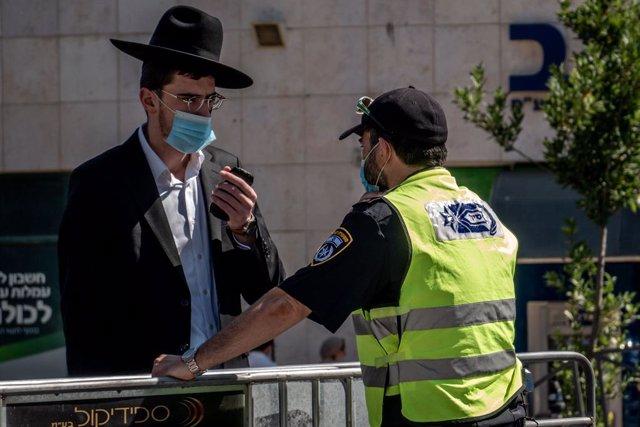 Archivo - Un policía de Israel junto a un hombre durante la pandemia de coronavirus