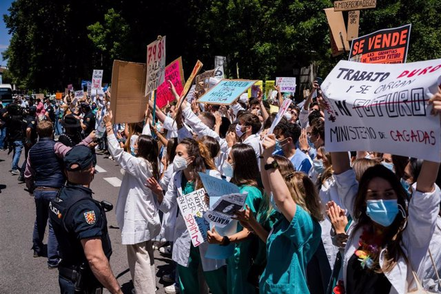 25 May 2021, Spain, Madrid: Police trying to push back protesters during the Resident Internal Doctors (MIR) demonstration in front of the Spanish Ministry of Health, to show their rejection of the new requirements for the choice of specialized health tra