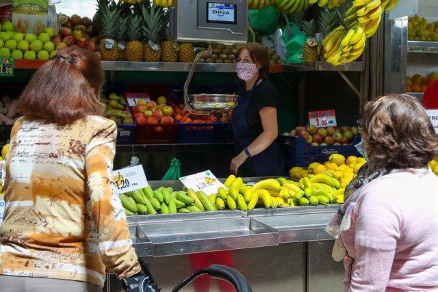 Archivo - Una trabajadora de una frutería del Mercado Central de Valencia atiende a dos clientas después de que el Ministerio de Sanidad autorizara a que la totalidad de la Comunidad Valenciana pasase en su conjunto a la fase 1 de la desescalada, en Valen