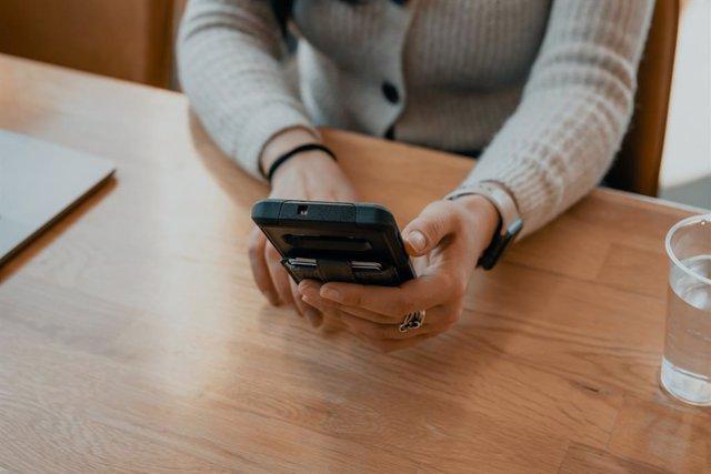 Mujer usando un smartphone con tarjetas.