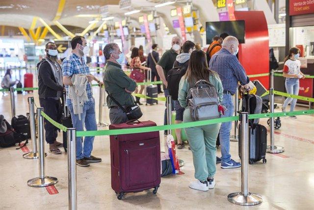 Varias personas hacen fila con maletas en la terminal T4 del Aeropuerto Adolfo Suárez Madrid-Barajas, a 21 de mayo de 2021. El presidente del Gobierno, ha anunciado este viernes que España permitirá a partir del próximo 7 de junio la entrada a los viajero
