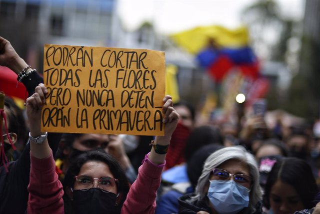 """28 May 2021, Colombia, Bogota: A woman holds a placard saying """"Maybe they can cut away all the flowers, but they will never stop the spring,"""" during a protest against the government of President Ivan Duque Marquez. Photo: Sergio Acero/colprensa/dpa"""