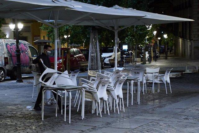 Una persona recoge la terraza de una cafetería en Madrid durante la primera jornada en la que se permite el cierre a la 01.00 en hostelería y recintos culturales, a 31 de mayo de 2021, en Madrid (España).