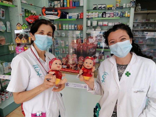 Cristina Gervasini, farmacéutica titular, y Mamen Ridruejo, farmacéutica adjunta, con los Baby Pelones de Juegaterapia.