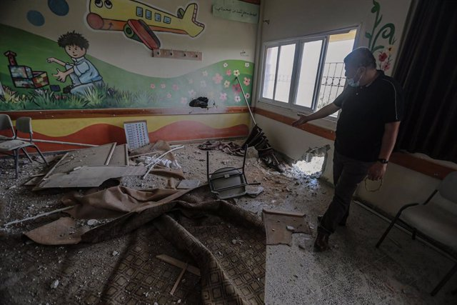 30 May 2021, Palestinian Territories, Gaza City: An employee of the Palestinian Ministry of Education inspects a damaged classroom inside a school that was hit during the recent Israeli airstrikes on the Zeitoun neighbourhood in Gaza City. Israel and the