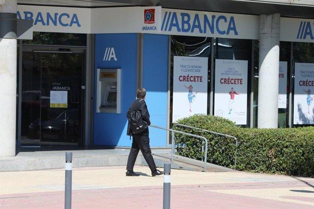 Archivo - Un hombre pasa al lado de una sucursal de Abanca, en Madrid, (España), a 10 de septiembre de 2020.