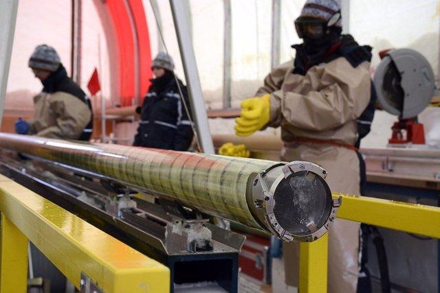 Perforadores de hielo con un núcleo de hielo recién perforado en el proyecto de núcleo de hielo del Polo Sur (SPICEcore).