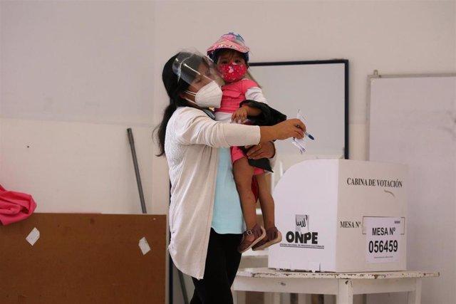 Archivo - Una mujer deposita su voto en la primera vuelta de las elecciones en Perú