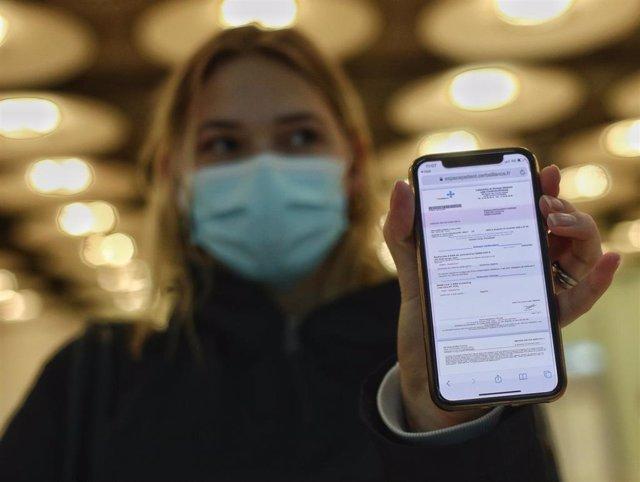 Una mujer de nacionalidad francesa enseña el negativo de su PCR  en un aeropuerto.