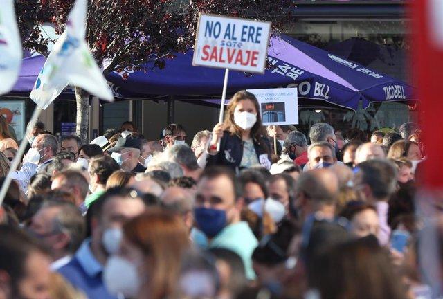 """Una mujer con un cartel en el que se lee: """"No al ERE salvaje"""" durante una concentración contra el ERE de Caixabank en las Torres Kio de Plaza de Castilla, a 20 de mayo de 2021, en Madrid (España)."""