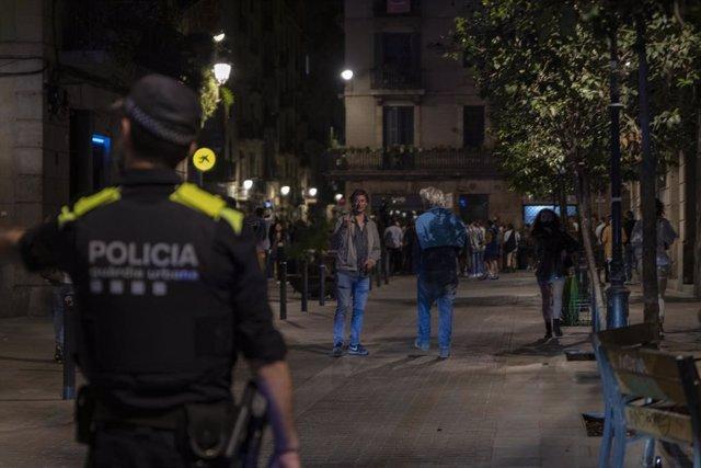 Agents de la Guàrdia Urbana de Barcelona, enfront de joves en ambient festiu, a 22 de maig de 2021, a Barcelona, Catalunya (Espanya).