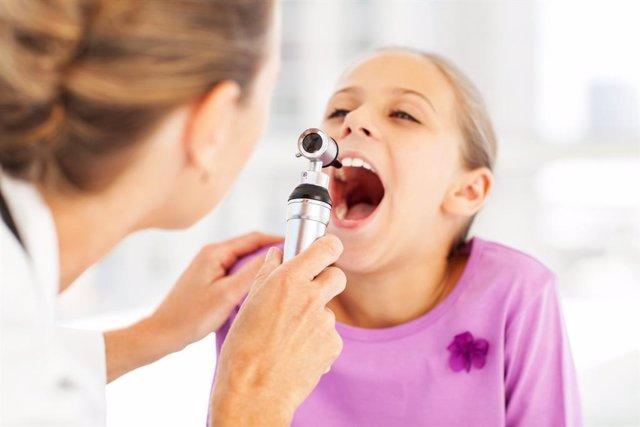 Archivo - Doctora mirando la garganta a una niña.
