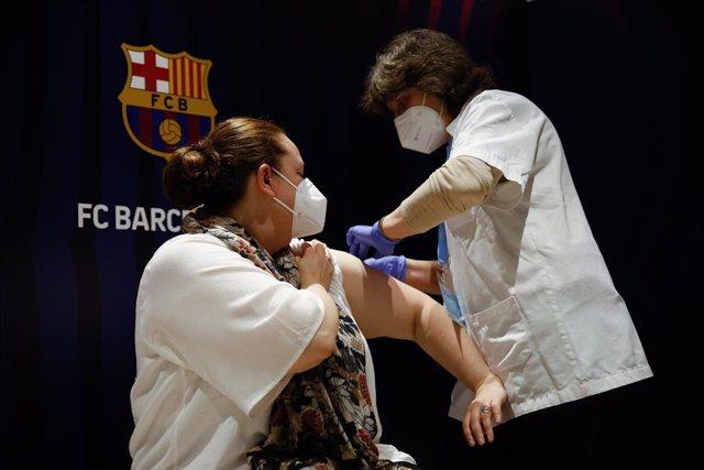 Una dona rep la primera dosi de la vacuna de Pfizer contra el Covid-19, a 27 de maig de 2021, a la Sala Berlín de l'estadi Camp Nou, a Barcelona.