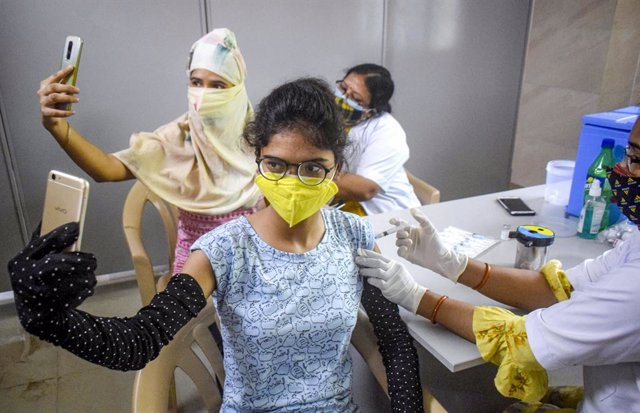 03 June 2021, India, Allahabad: Beneficiaries take selfies while receiving their COVID-19 vaccine jabs at Moti Lal Nehru Medical College vaccination center. Photo: Amar Deep Sharma/PTI/dpa