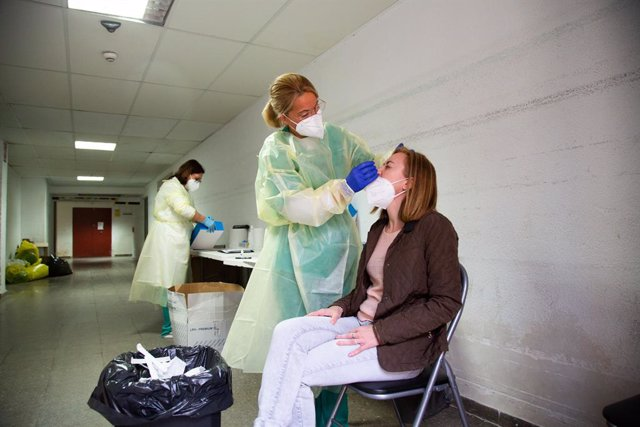 Archivo - Una sanitaria realiza un test de antígenos o una PCR a una mujer, en un dispositivo de cribado masivo instalado en el Hospital Perpetuo Socorro, en Badajoz, Extremadura (España), a 1 de abril de 2021. Este miércoles ha comenzado la segunda fase