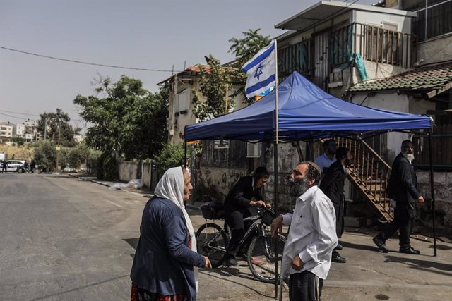 10 May 2021, Israel, Jerusalem: People speak together in front of a tent with the Israeli flag at Jerusalem's Sheikh Jarrah neighbourhood. Some Palestinian families in Sheikh Jarrah are facing eviction from their homes by Israeli authorities, further heig