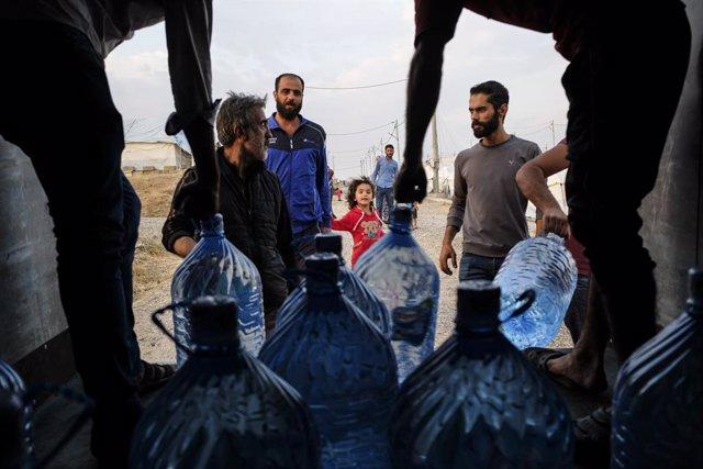 Archivo - Reparto de garrafas de agua entre refugiados en Irak, en octubre de 2019