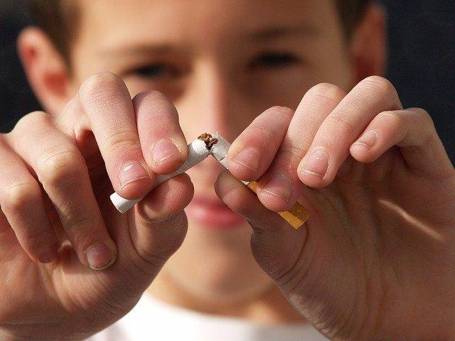 Adolescente rompiendo un cigarrillo.