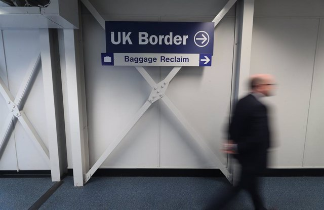 Archivo - 11 June 2020, Northern Ireland, Belfast: A man passes a UK border sign at Belfast International Airport which reopens on 15 June 2020. Photo: Niall Carson/PA Wire/dpa