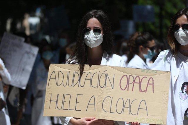 """Una mujer sujeta un cartel en el que se lee: """"Adjudicación opaca huele a cloaca"""", en la manifestación convocada por la plataforma FSE Unida como protesta al sistema de adjudicación de plazas para el MIR este año frente al Ministerio de Sanidad, a 25 de ma"""