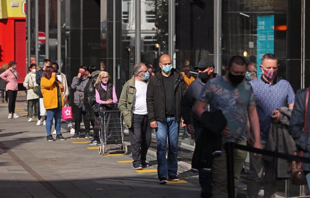 17 May 2021, United Kingdom, Dublin: Shoppers queue in front of a store in Henry Street as Ireland takes another step towards normality with all non-essential retail being allowed to resume. Photo: Niall Carson/PA Wire/dpa